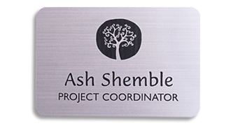 An aluminum name tag with a black logo and text.