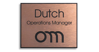 A copper colored name tag with a black logo and text.