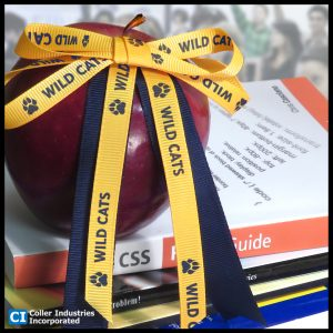 Custom ribbons with a school mascot and logo attached to an apple, used to increase student engagement.