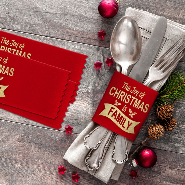 Custom badge ribbons personalized for a holiday family party wrapped around a table setting.